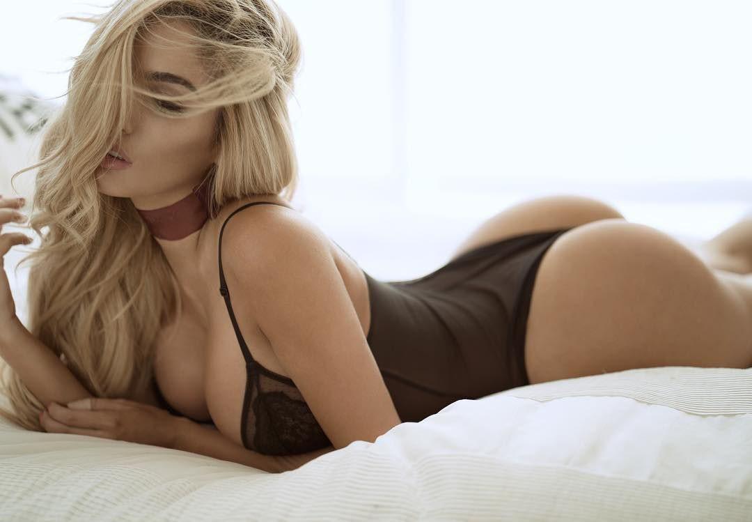 Фото красивых девушек - блондинка с длинными волосами лежит в кровати на белой простыне